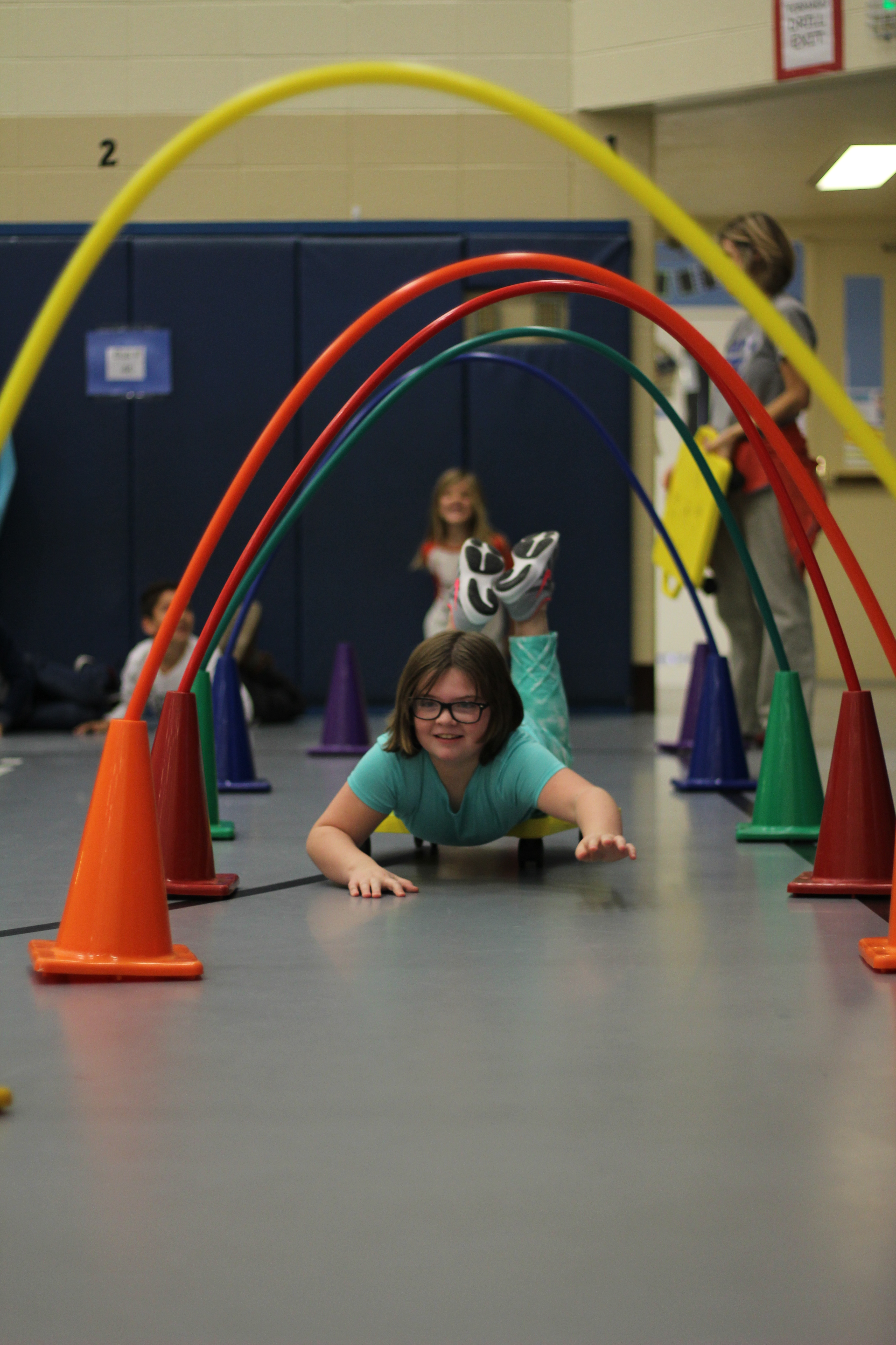 A student rolls through the obstacle course