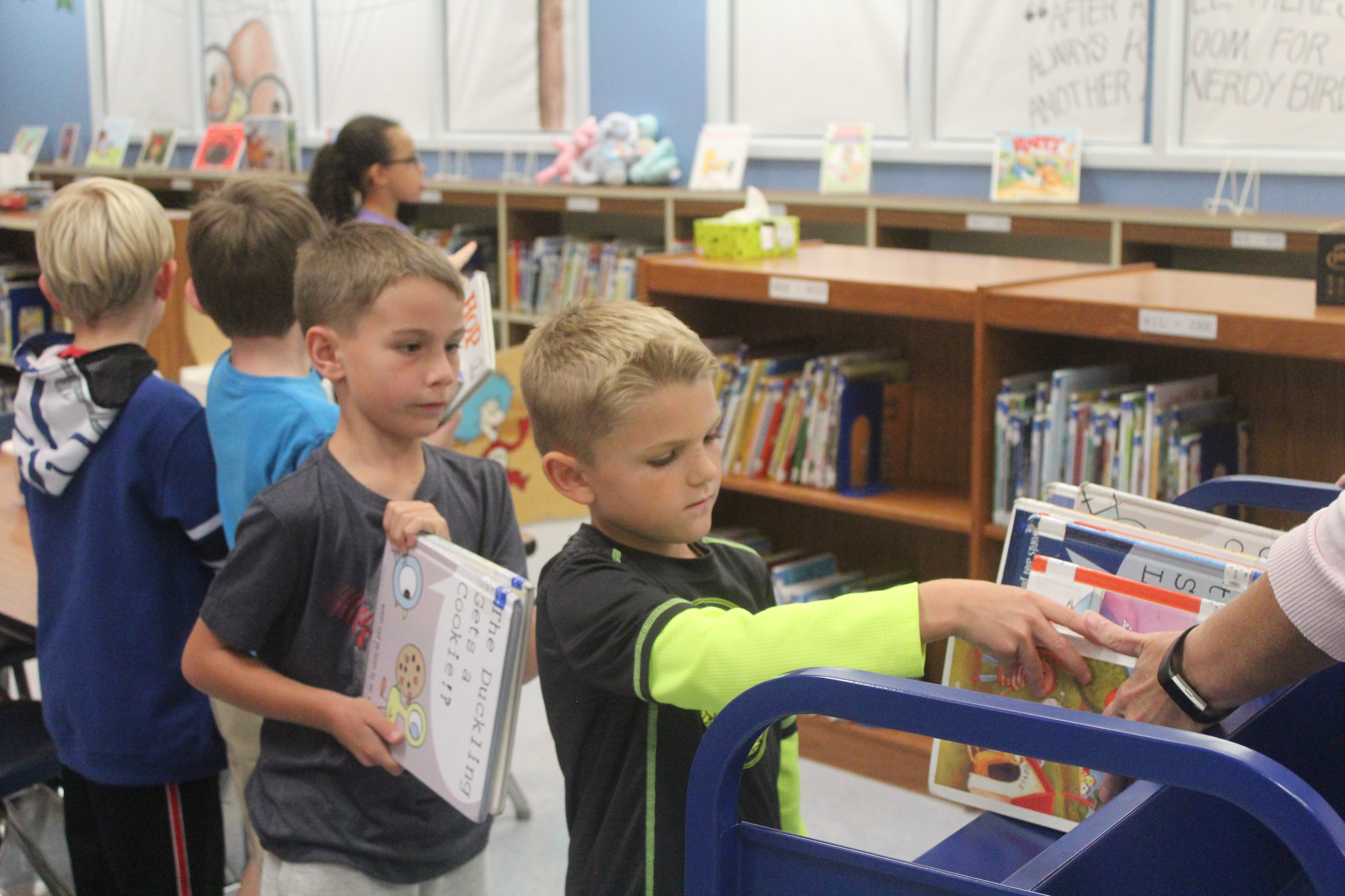 A kid places his library books on the cart to be returned.