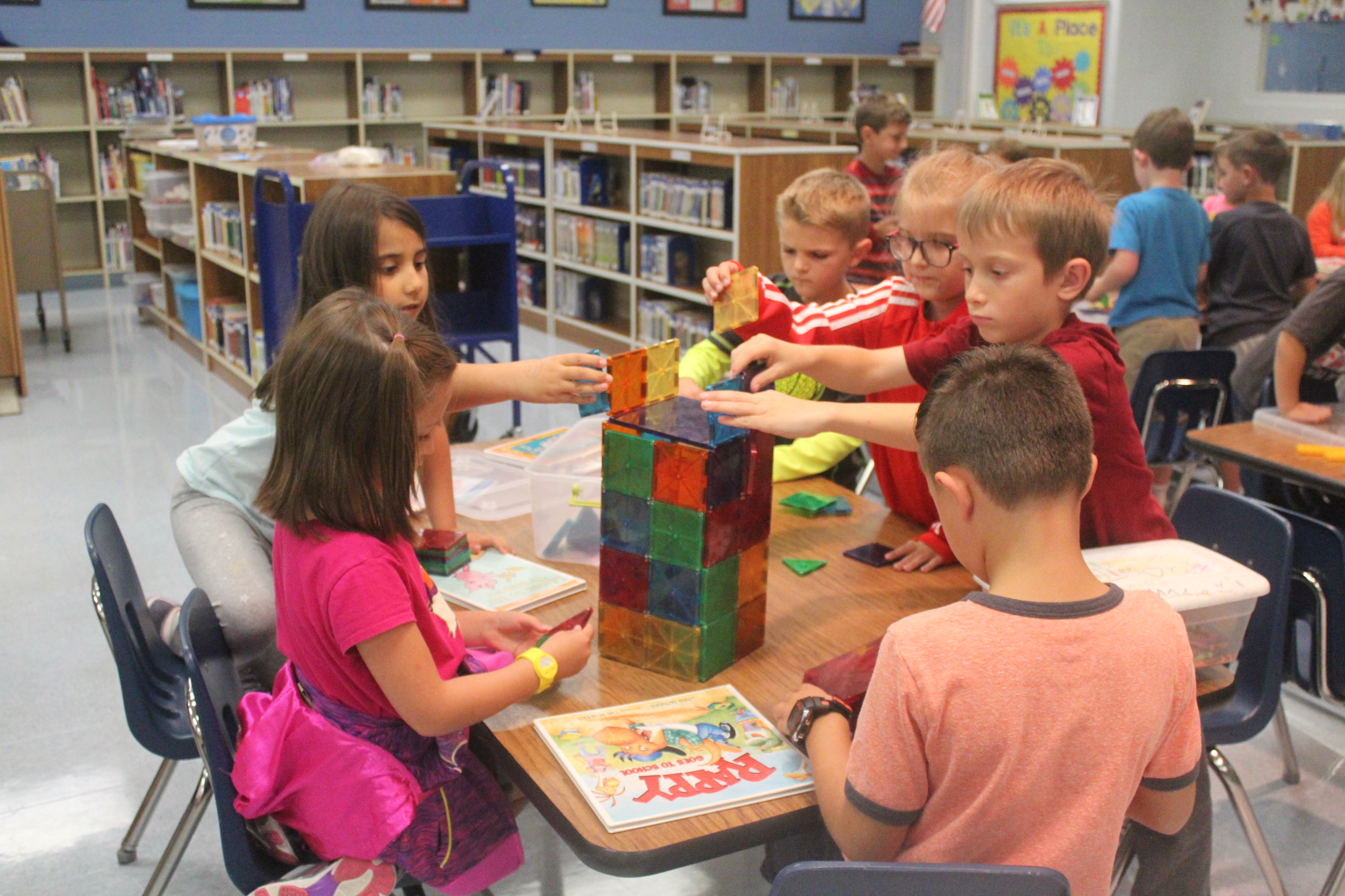 Kids play with magnetic blocks in the library.