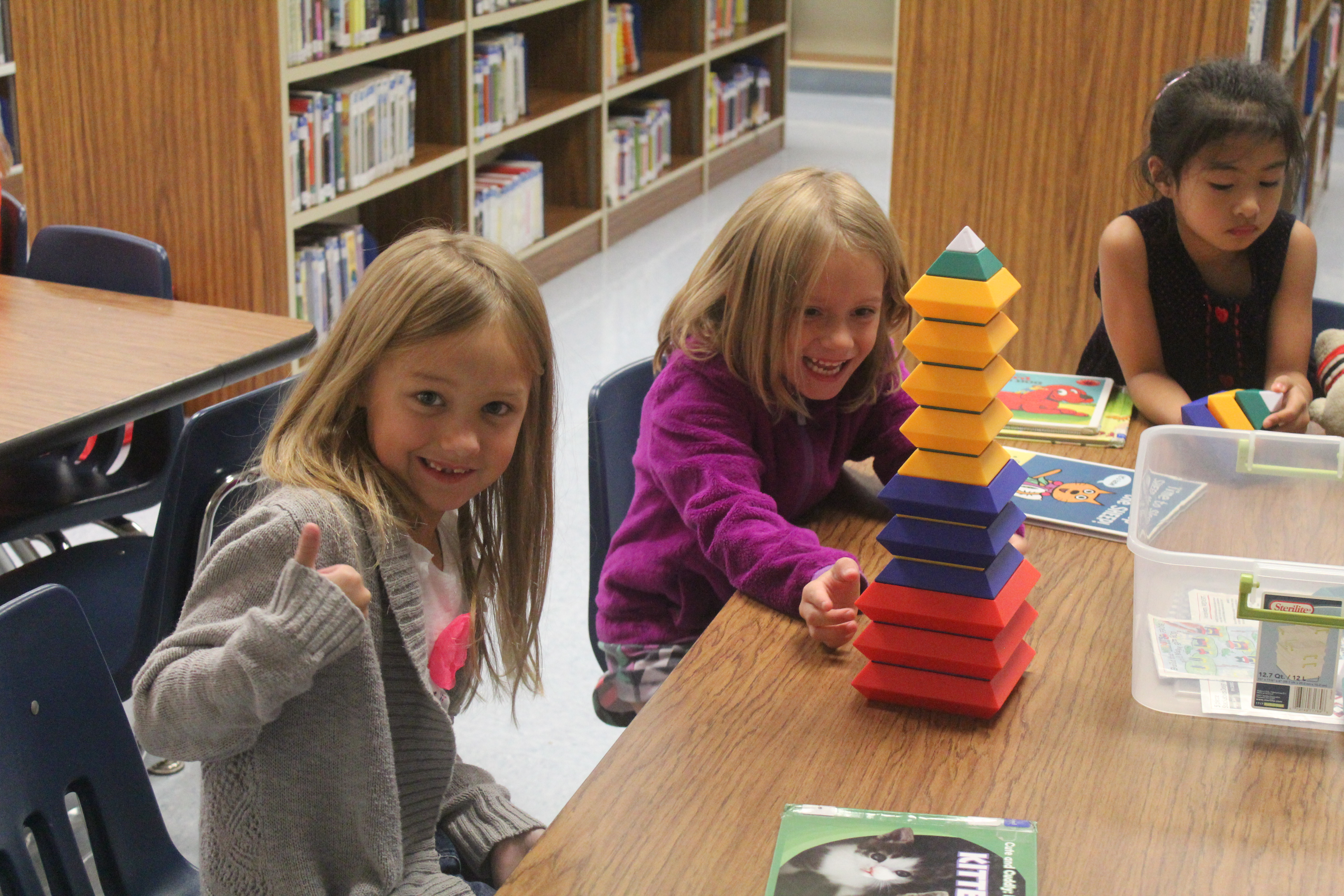 Two girls from Mrs. Extin's first grade class make pyramids with blocks.