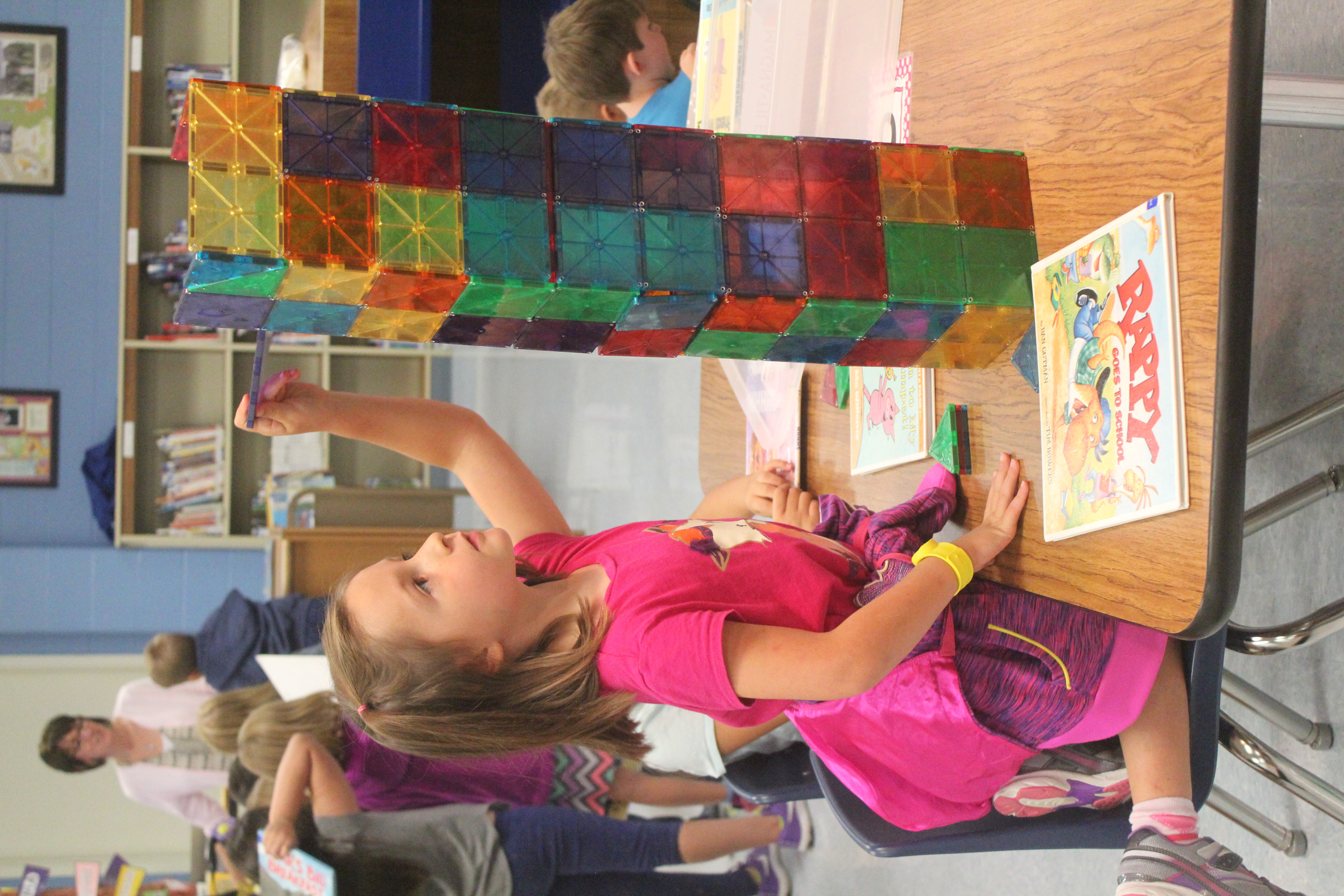 A girl helps build a tower with magnetic blocks in the library.