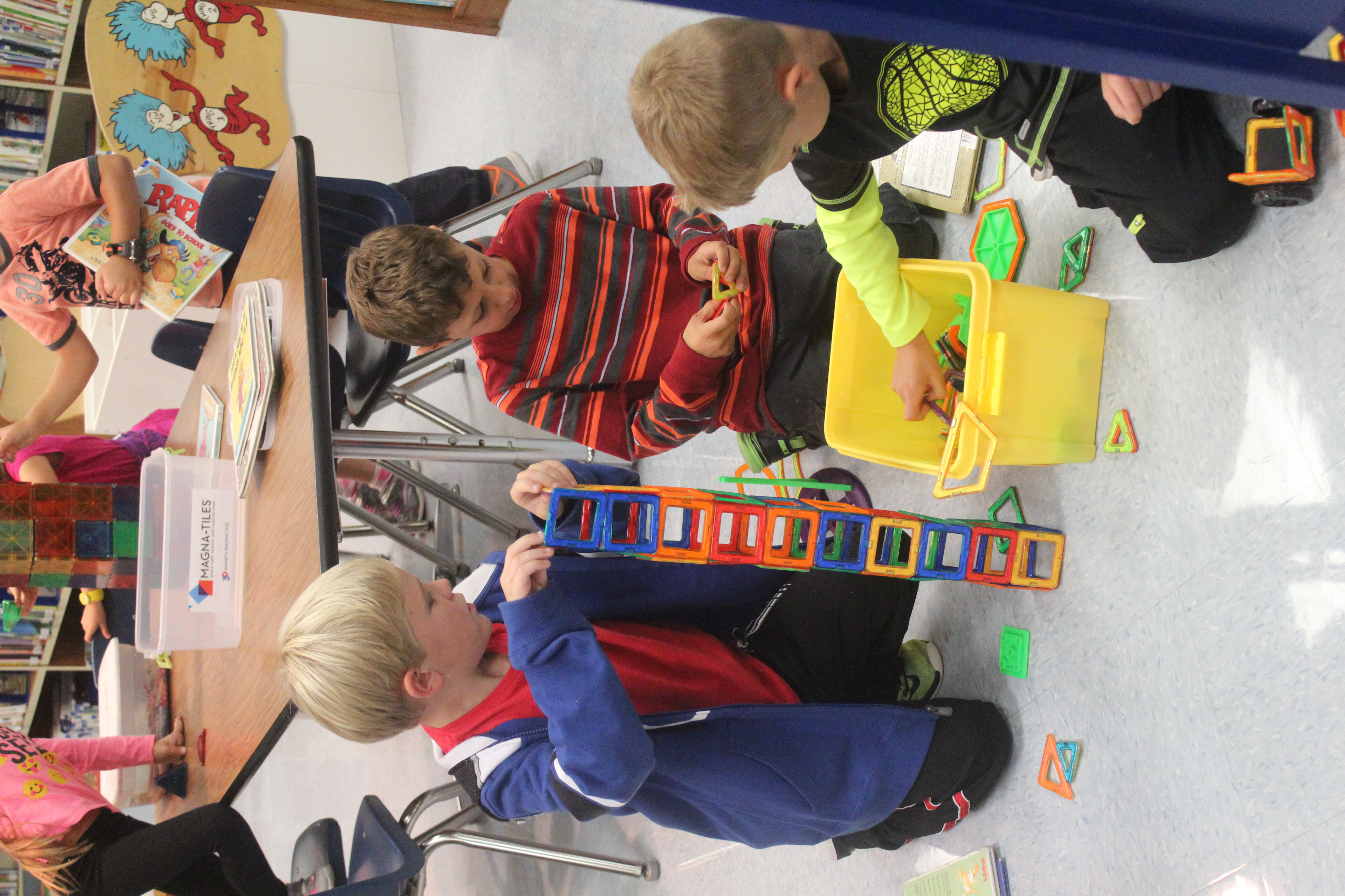 Three boys build a tower with magnetic blocks.