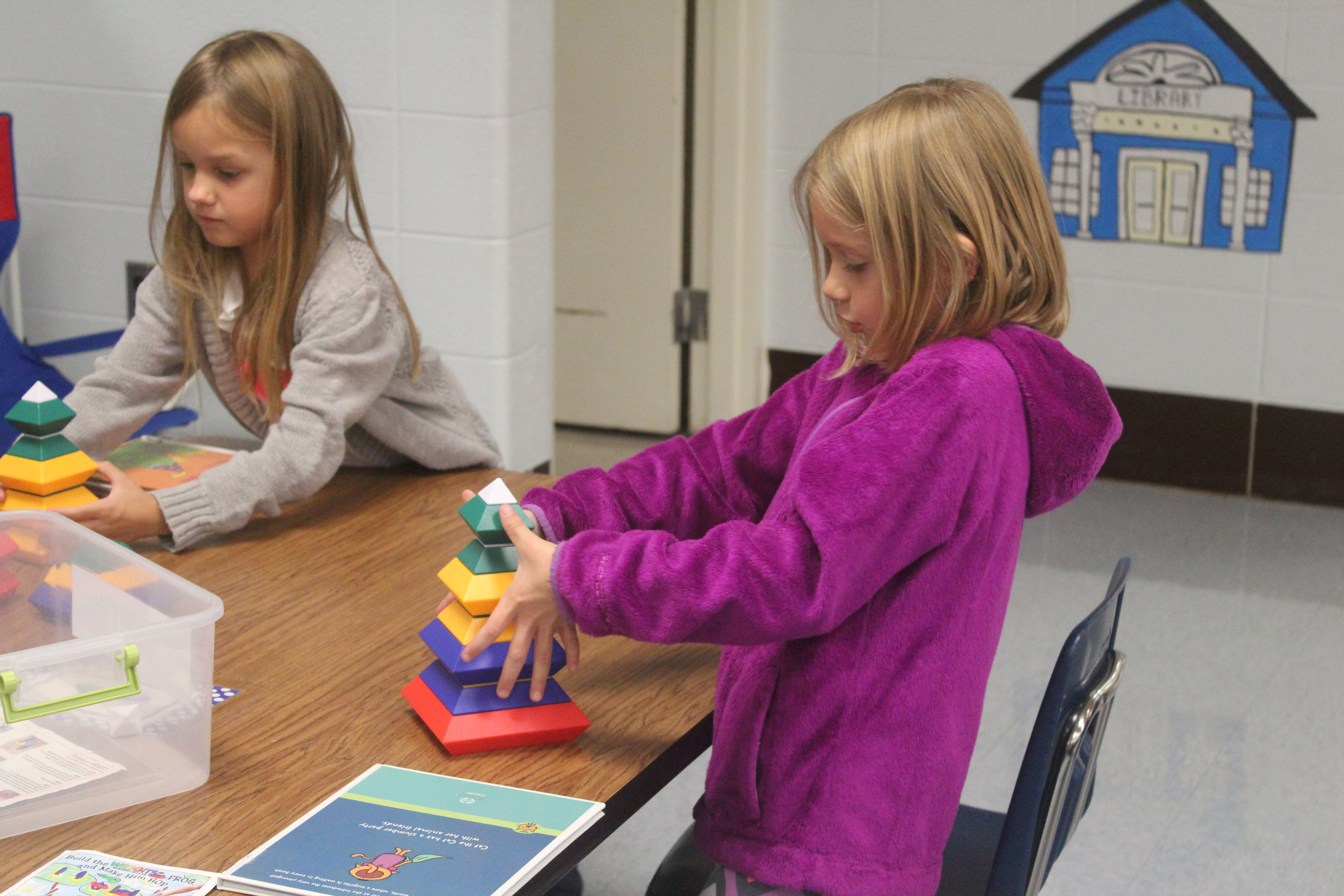 A girl plays with pyramid blocks during her time in the library.