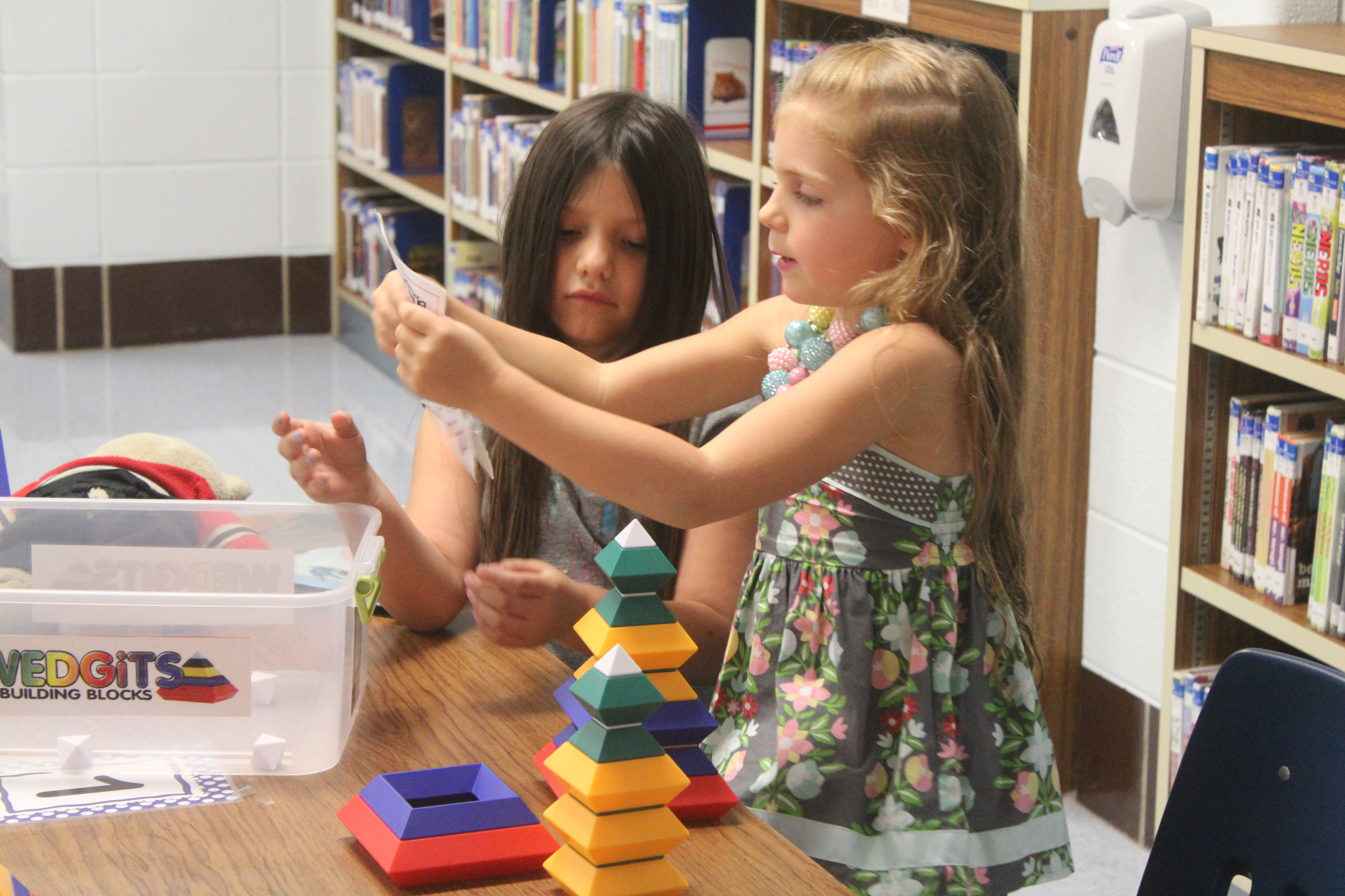 Two girls from Mrs. Extin's class read instructions to the blocks.