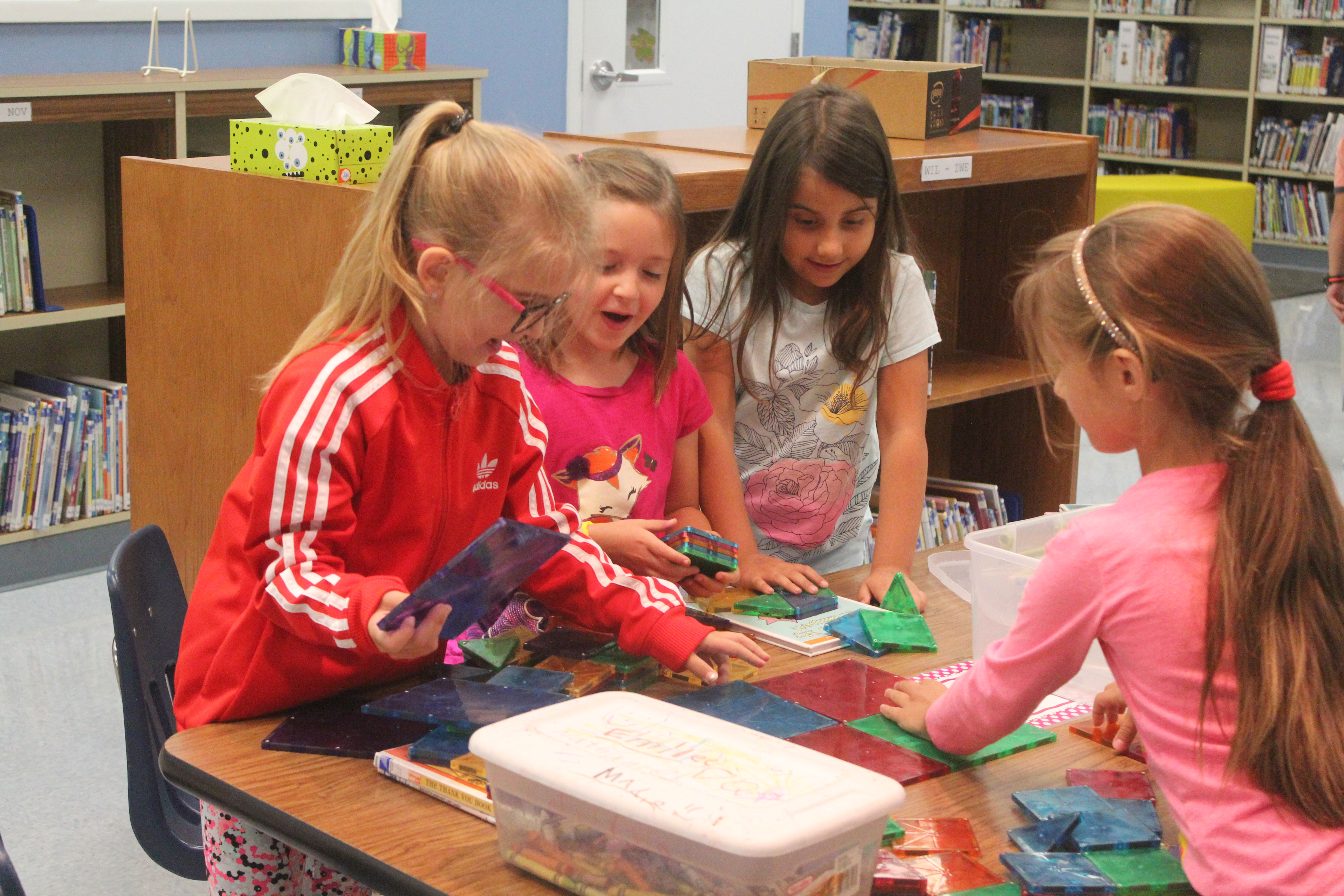Four first graders help build a tower with magnetic blocks.