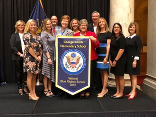 """please post. """"Mrs. Logan and a representative team of teachers proudly accept the National Blue Ribbon School banner from State Superintendent of Public Instruction, Dr. Jennifer McCormick on Tuesday October 2, 2018 at the Statehouse."""