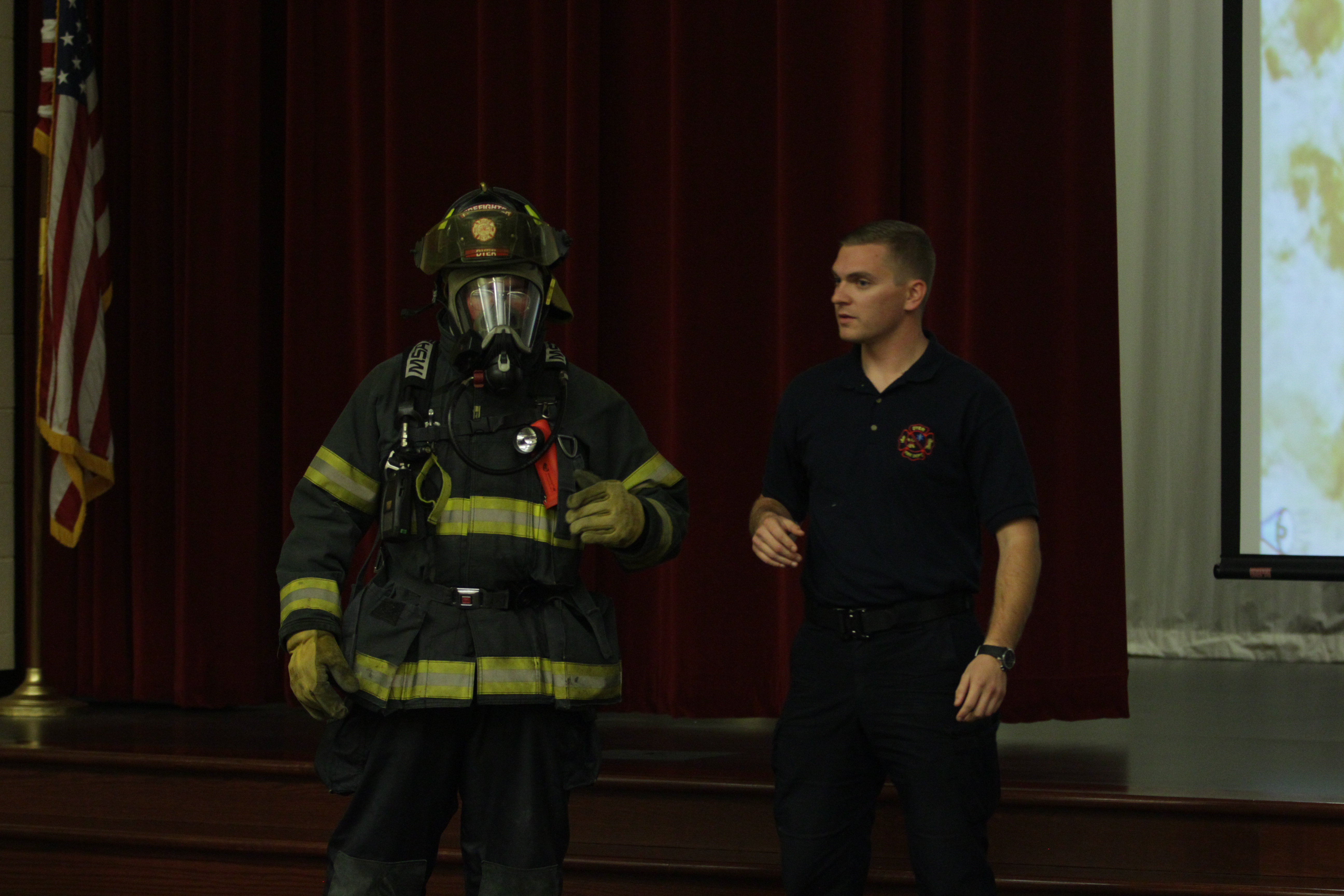 The firefighter demonstrates how to use a breathing tube