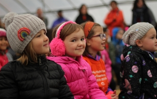 Students smile as they watch a puppet show