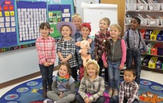 A Kindergarten class smiles.