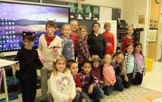 A second grade class smiles.