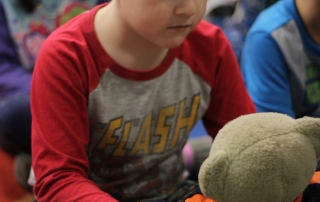 A student holds a stuffed bear