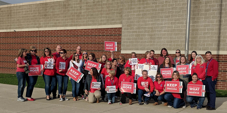 "Clark MS Staff poses for a picture after their ""Red for Ed"" gathering before school on April 24, 2019."