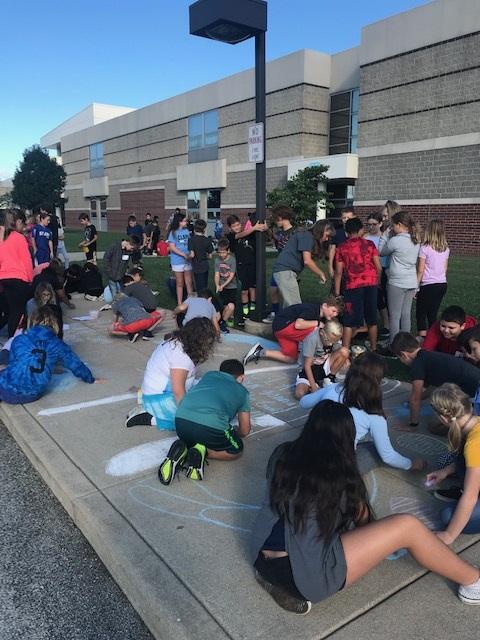 Clark advisory classes complete their sidewalk chalk drawing activity for school spirit week.