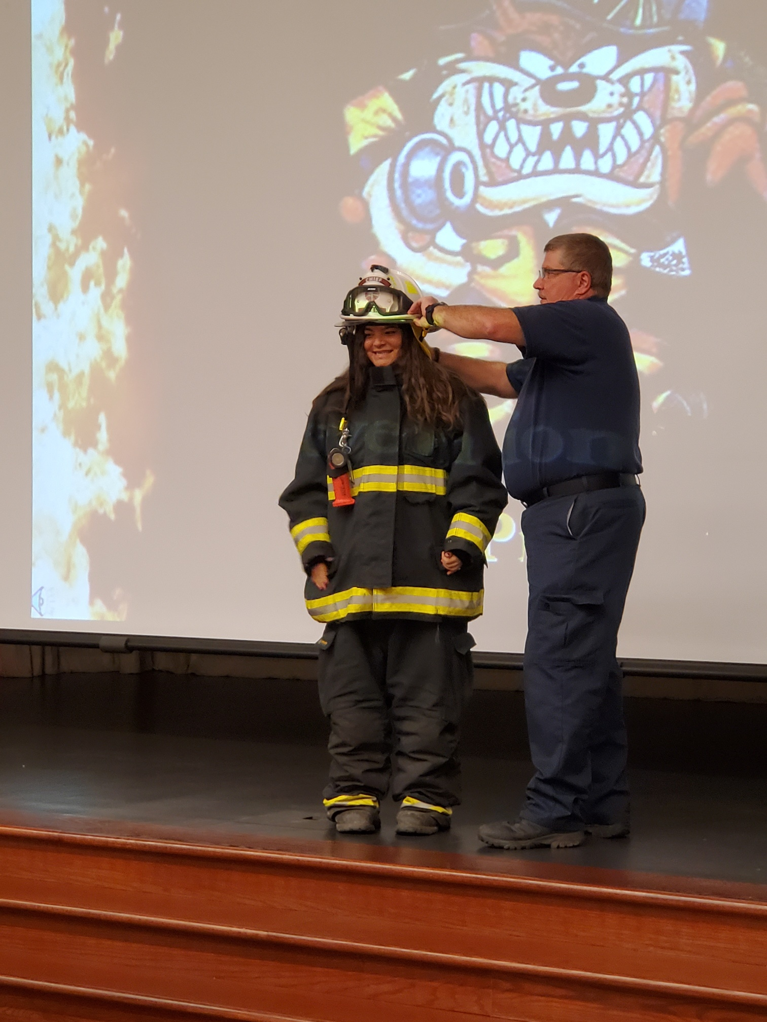 Protsman Kindergarten teacher Melissa Ballenger gets to try on protective fire gear with assistance from Dyer FD Chief Thad Stutler during a fire safety presentation on October 7, 2019.