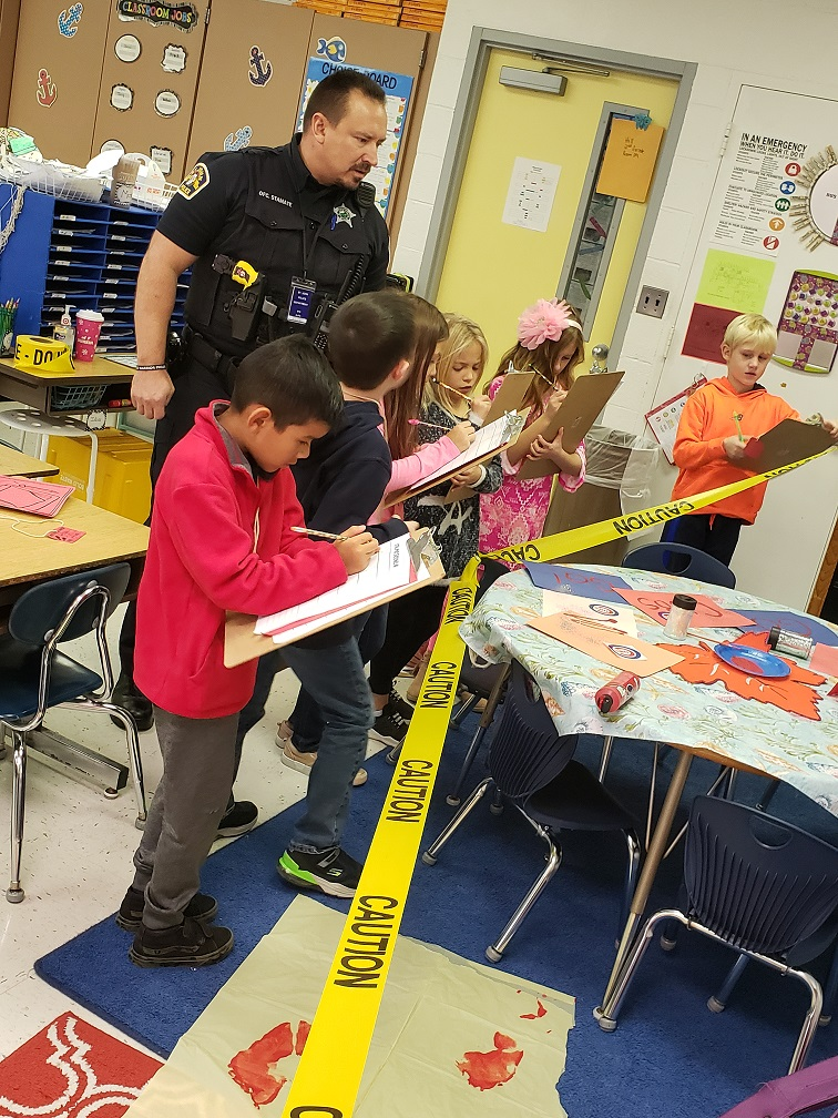 Mrs. Hill's students at Kolling are taught how police use inference at a crime scene by Lake Central SRO Nick Stamate.