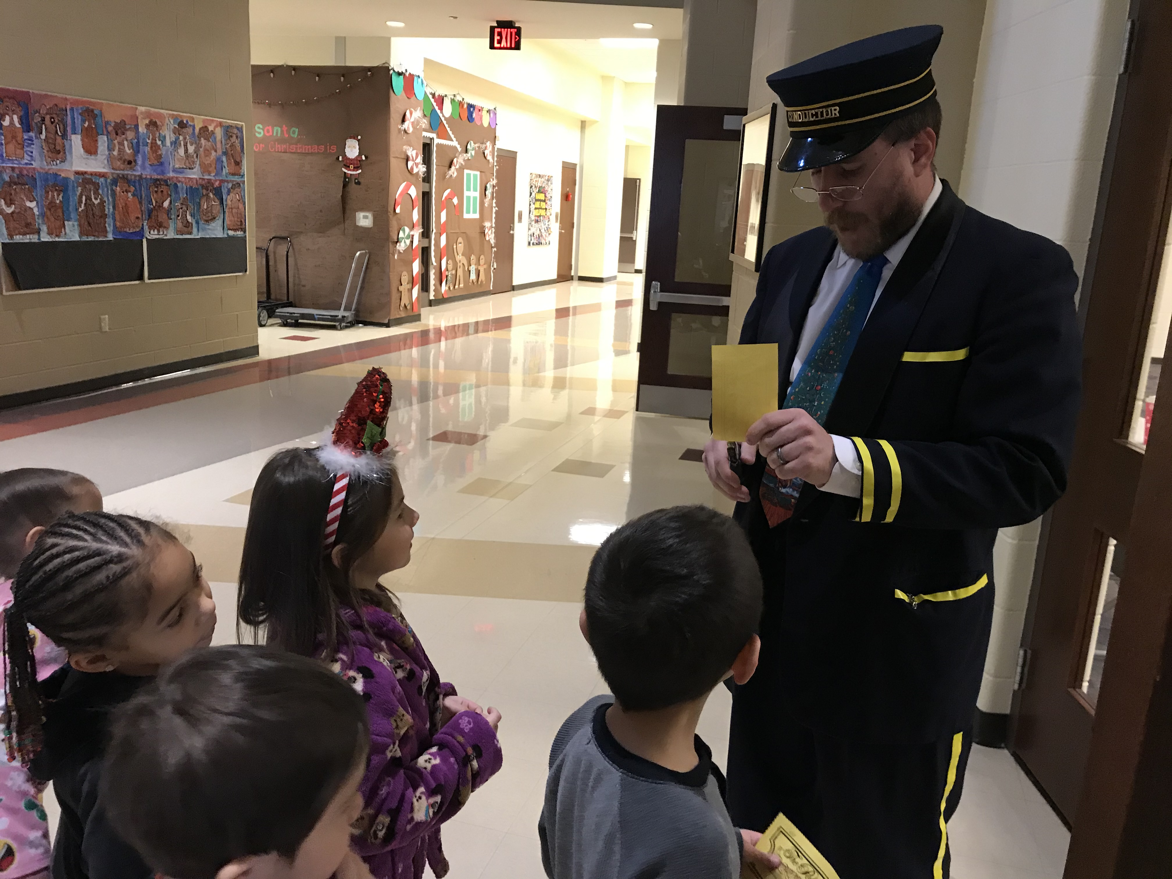All aboard the Polar Express! Protsman Kindergarteners, get their tickets punched and entering the train so the conductor can read Polar Express.